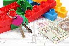 Le chiavi domestiche, le particelle elementari variopinte ed i soldi su alloggio progettano Fotografia Stock Libera da Diritti