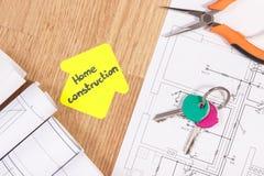 Le chiavi domestiche, le pinze del metallo, i disegni elettrici e la casa modellano con il conctruction della casa del testo, svi Fotografia Stock