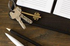 Le chiavi su un taccuino e su una penna, disegnano a matita la vista superiore Fotografie Stock Libere da Diritti