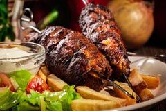 Le chiche-kebab grillé a servi avec les frites et la salade frites Photo stock