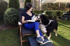 Le chien apporte la bière à son propriétaire que la femme dehors font du jardinage tenant des amis Photo stock