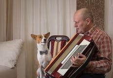 Le chien de Basenji et le musicien mûr avec l'accordéon disposent à effectuer apprendre la nouvelle chanson photos libres de droits