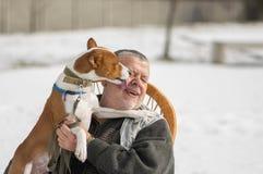 Le chien de Basenji lèche le maître le déchargeant des obligations quotidiennes du ` s pour le chef Photographie stock libre de droits