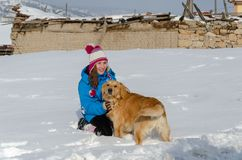 Le chien de golden retriever joue avec la fille sur la neige en hiver photos libres de droits