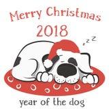Le chien dort sur l'oreiller dans le chapeau de Santa Photos stock