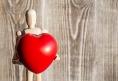 Le chiffre d'un homme en bois tient un coeur rouge dans des ses mains Photographie stock