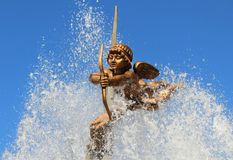 Le chiffre du cupidon avec un tir à l'arc sur lequel écoulements d'eau de la fontaine photos libres de droits