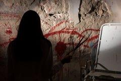 Le chiffre femelle ombragé tenant la lame près du sang a souillé le mur photographie stock