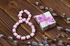 Le chiffre-huit a garni du boîte-cadeau rose de vert de guimauve avec les branches pourpres de ressort de ruban avec des bourgeon Photo stock