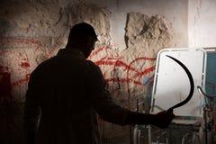 Le chiffre ombragé tenant la faucille dans le sang avant a souillé le mur photos libres de droits