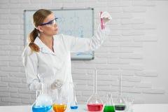 Le chimiste fait et expérience avec des substances dans les tubes et les pipetts Photographie stock libre de droits