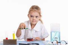 Le chimiste fou verse le liquide vert dans un flacon Photo stock