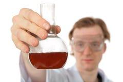 Le chimiste retient le flacon avec le liquide brun photo stock