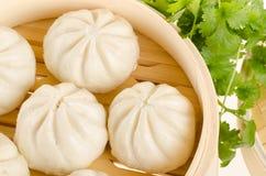 Le Chinois a cuit des petits pains à la vapeur dans le panier en bambou de vapeur avec le cilantro sur W Photo stock