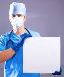 Le chirurgien dans le masque tient une plaquette Photo stock