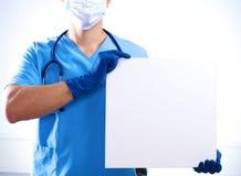 Le chirurgien dans le masque tient une plaquette Images libres de droits