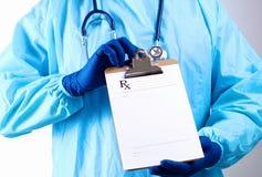 Le chirurgien dans le masque tient une plaquette Image stock