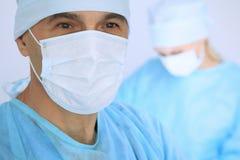 Le chirurgien de patron examine l'opération tandis que l'équipe médicale sont occupée du patient Médecine, soins de santé et urge image libre de droits