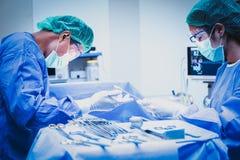 Le chirurgien et l'assistant fonctionnent dans la salle d'opération photographie stock