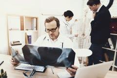 Le chirurgien expérimenté avec le stéthoscope diagnostique le patient regardant le rayon X image libre de droits