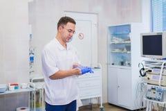 Le chirurgien mûr beau dans l'usage et le masque médicaux bleus met les gants médicaux à la salle d'opération Photographie stock