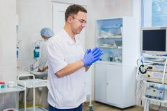 Le chirurgien mûr beau dans l'usage et le masque médicaux bleus met les gants médicaux à la salle d'opération Image stock