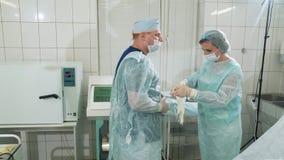 Le chirurgien met dessus les gants propres avant l'opération, les aides d'infirmière que le docteur les a mis dessus Les médecins clips vidéos