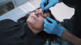 Le chirurgien plasticien vérifiant le milieu a vieilli le visage de femme avant la chirurgie esthétique clips vidéos
