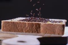 Le chocolat arrose sur un pain coupé en tranches image stock