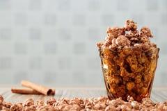 Le chocolat a assaisonné le maïs éclaté dans le verre jaune et sur la table en bois brune avec le fond de cannelle images stock