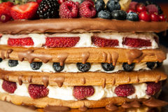 Le chocolat a complété le gâteau de couche d'éponge avec des baies Images libres de droits