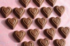 Le chocolat de forme de coeur rapièce dans les rangées sur le papier rose Images libres de droits