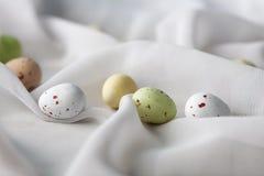 Le chocolat specled des oeufs de pâques dans des plis de tissu de gaze image stock