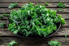 Le chou frisé végétal de superfood sain vert frais part dans un plat noir sur la table rustique en bois Photo libre de droits