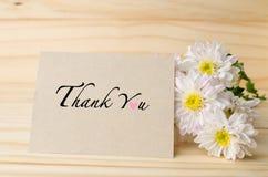 Le chrysanthème blanc fleurit avec vous remercient de carder sur la table en bois photo stock