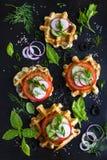 Le cialde saporite con formaggio, il prosciutto, olive ed erbe, sono servito con la f immagini stock