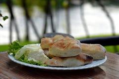 Le ciambelle del pane fresco con formaggio cremoso sono servito sul piatto bianco all'aperto Immagine Stock