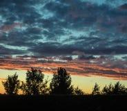 Le ciel au coucher du soleil est pointillé avec des nuages images stock