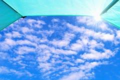 Le ciel bleu avec les nuages et le soleil blancs rayonne vu de l'intérieur d'une tente Photo stock