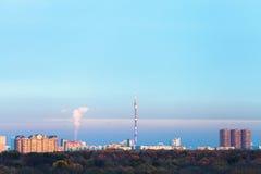 Le ciel bleu de coucher du soleil au-dessus des maisons urbaines et la TV dominent Photos libres de droits