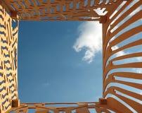 Le ciel bleu et le contre-plaqué avec des trous ont coupé Image stock
