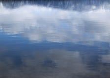Le ciel bleu et les nuages abstraits se sont reflétés dans l'eau de lac Image stock