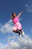 Le ciel est le saut de limite pour la joie par la jeune fille d'école Photos stock