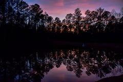 Le ciel et les arbres d'été se sont reflétés dans l'eau de lac Photo stock