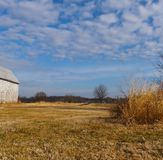 Le ciel, nuages, grange, blé, herbe, arbres jouent tout un rôle dans cette scène pittoresque de terres cultivables d'hiver image libre de droits