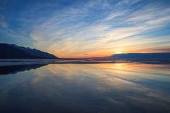 Le ciel nuageux et les réflexions dans l'eau apprêtent sur le lever de soleil Photo stock