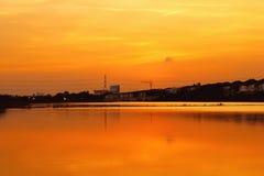 Le ciel orange crépusculaire opacifie la réflexion de l'eau photographie stock