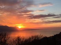 Le ciel rouge de coucher du soleil opacifie le lac Photographie stock libre de droits
