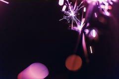 Le cierge magique lilas du Bengale s'allume sur un fond noir en l'honneur des célébrations de nouvelle année et d'anniversaire de Photos libres de droits