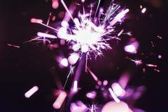 Le cierge magique lilas du Bengale s'allume sur un fond noir en l'honneur des célébrations de nouvelle année et d'anniversaire de Image libre de droits